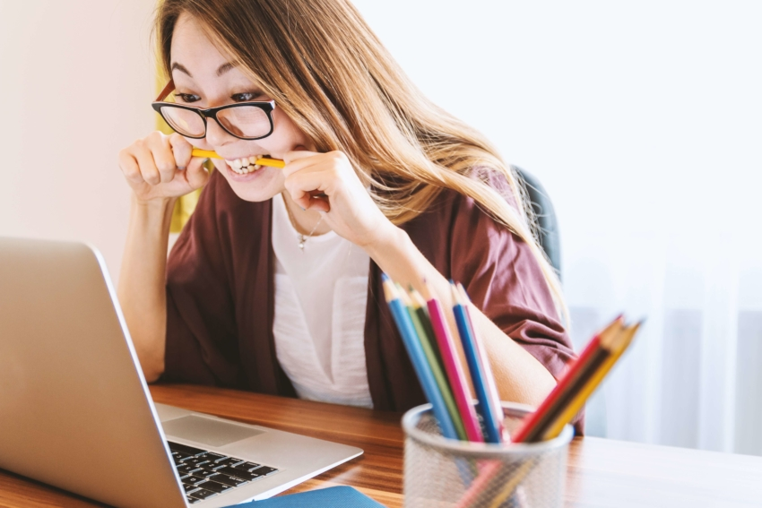 Woman biting a pencil while studying at laptop to avoid failing in college