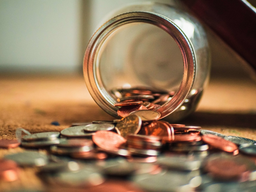 Jar spilled over with coins