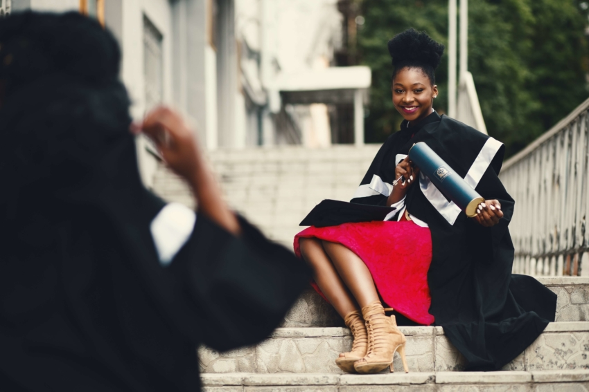 Woman holding degree on stairs