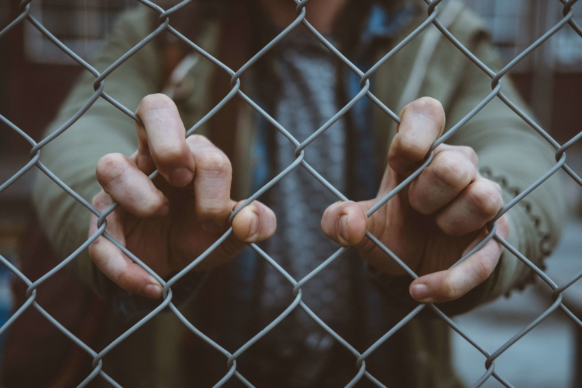 Student with both hands on chain link fence