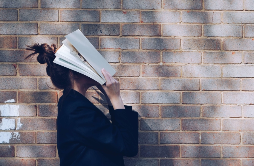 Student with book on her face
