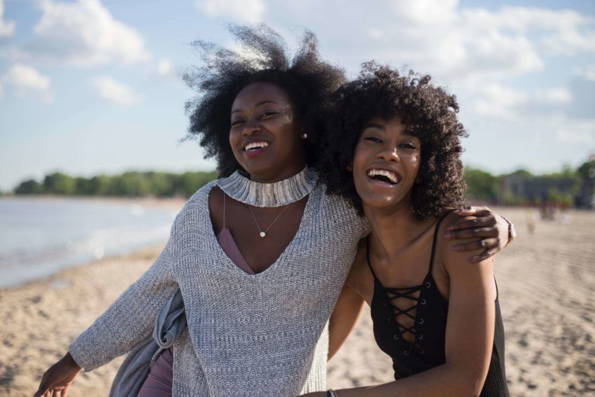 """""""Two female University of the People students smiling on a beach"""""""