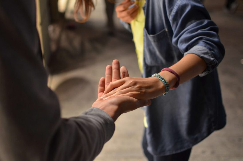 Friends with an outstretched hand offering support at UoPeople