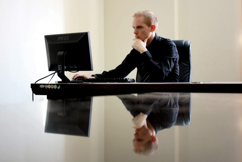 A man using his reflective thinking skills while sitting in front of his computer.