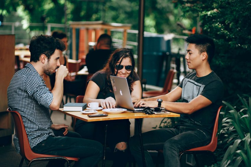 Group of three college students at a cafe