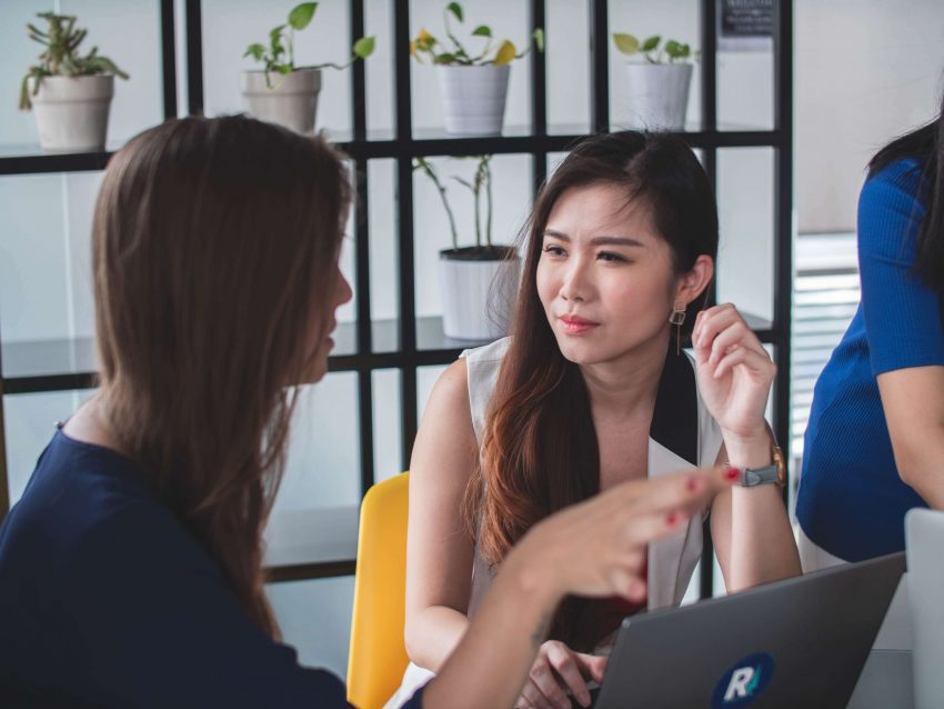 Girl actively listening to another girl in workplace
