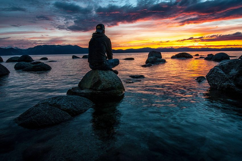 Watching the beautiful sunset while sitting on a rock and engaging in reflective thinking.