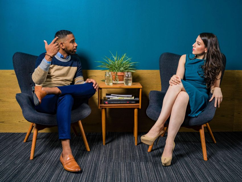 Man and women sitting down calmly dealing with conflict in mature way by having conversation instead of fighting