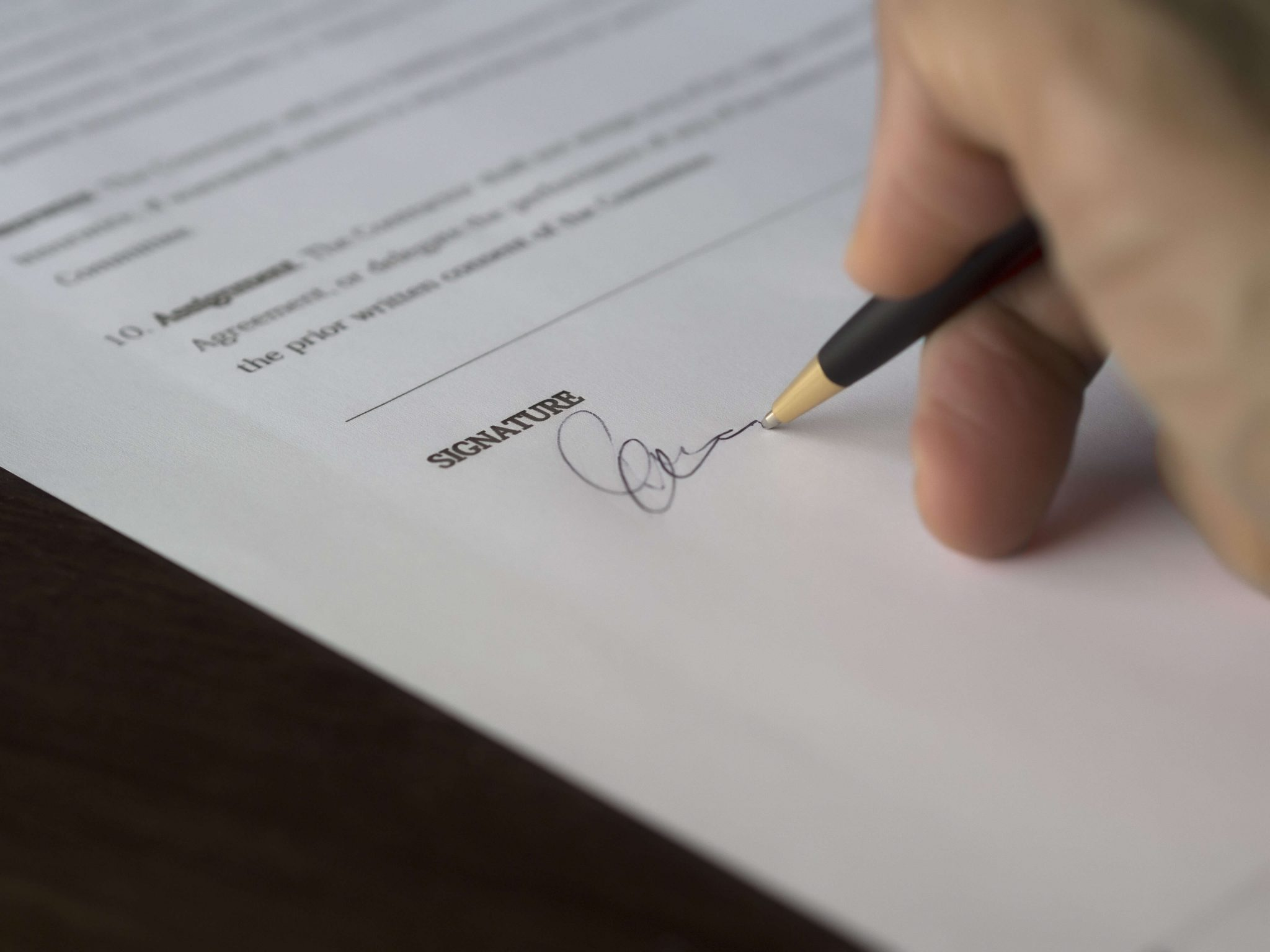 Signing a written contract with pen