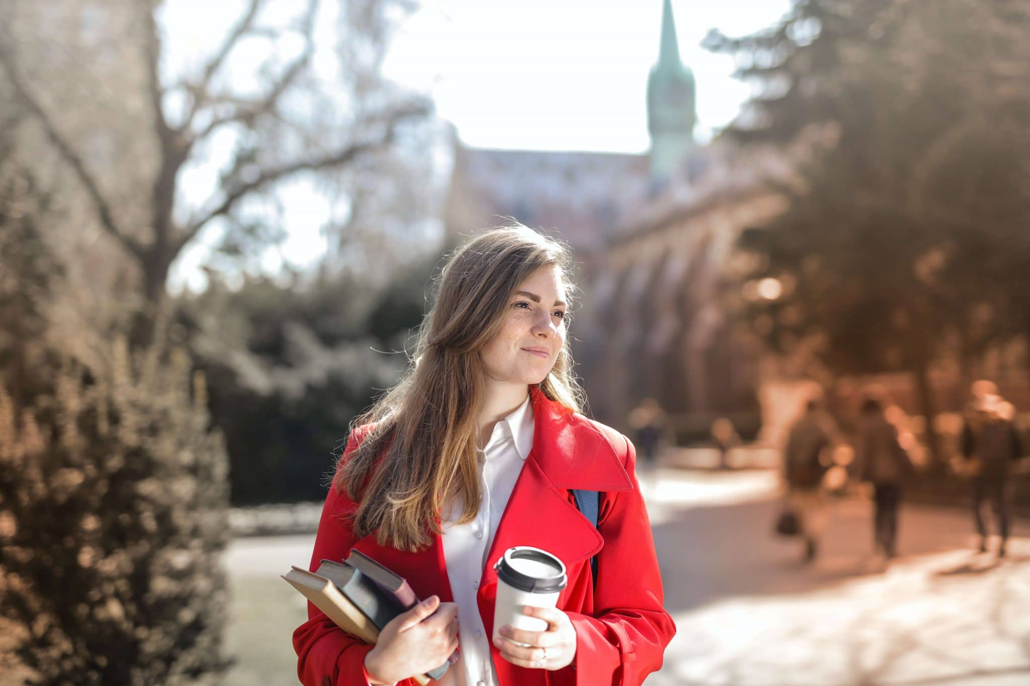 A female college student holding a coffee and some textbooks