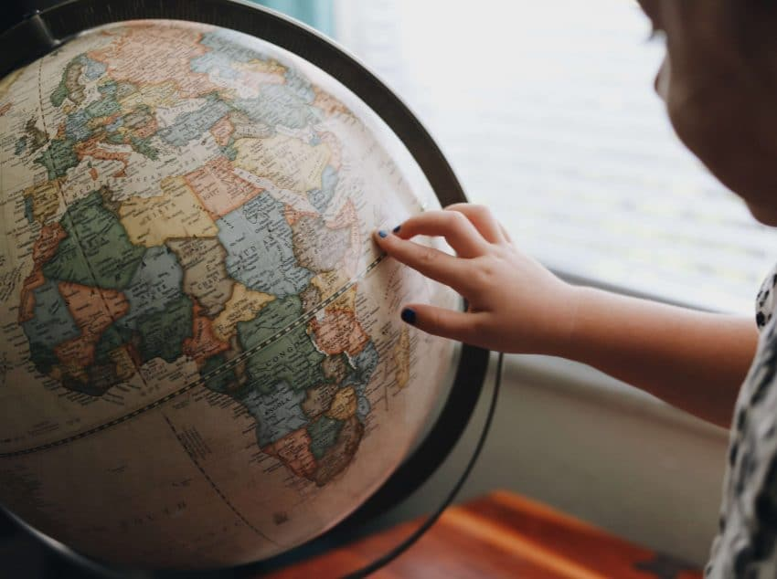 Child pointing finger on a globe