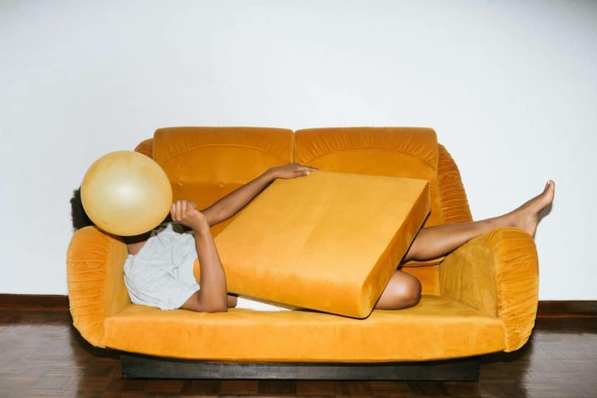 An introverted man lying on a yellow sofa covering his face with a balloon