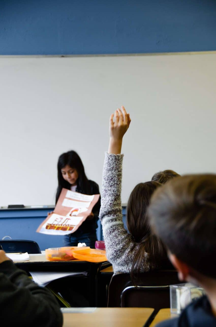 Student raising hand in a classroom