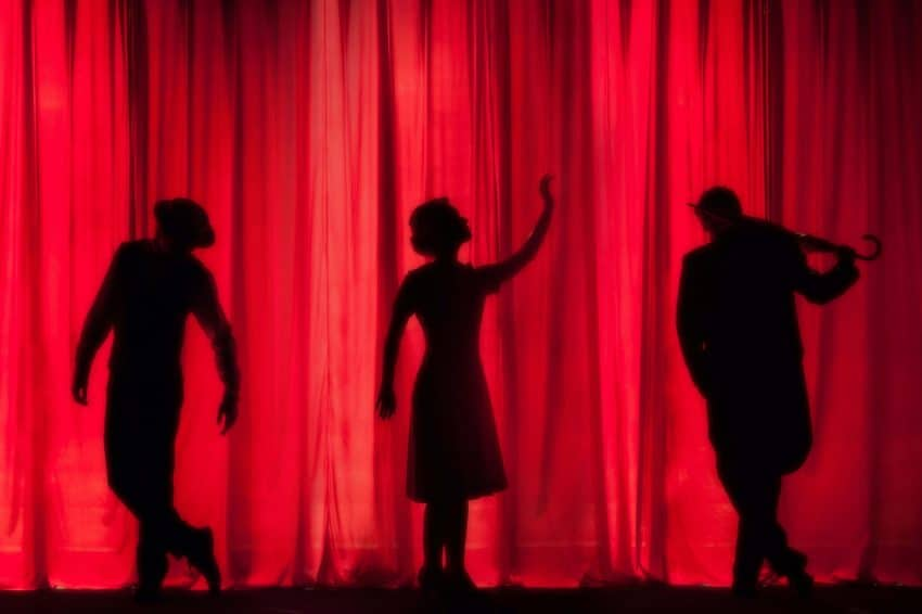 Silhouettes of actors on stage with a red curtain