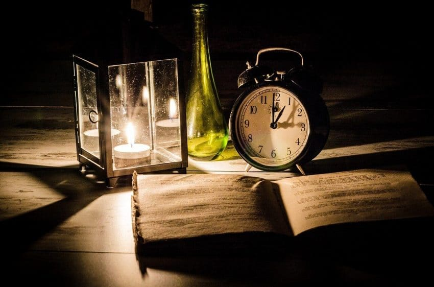 Late night, open book on desk in front of candle, clock, and vase, studying for a minor