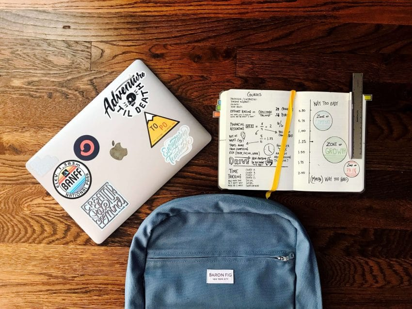 A backpack, laptop, and open notebook on a desk