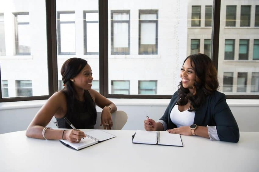 Two women in a meeting for tuition reimbursement